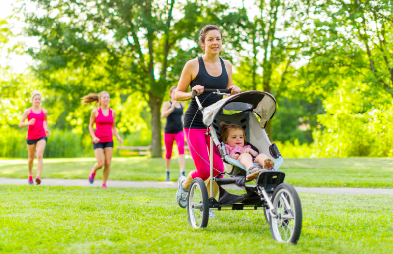 Woman pushing her little girl in a toddler while running outside with friends